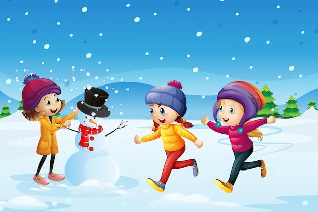 Tre bambini che giocano a pupazzo di neve nel campo di neve Vettore gratuito