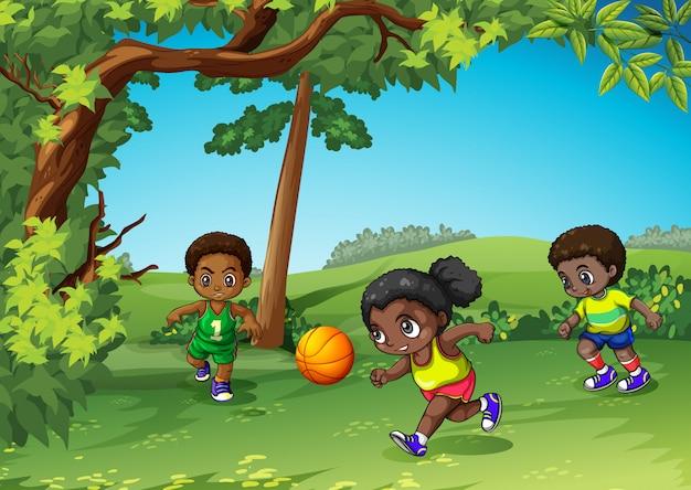 Tre bambini che giocano palla nel parco Vettore gratuito
