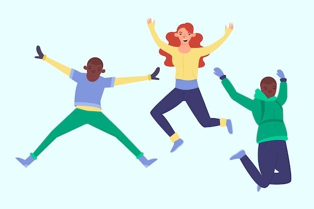 Tre giovani che indossano il salto dei vestiti di inverno Vettore gratuito