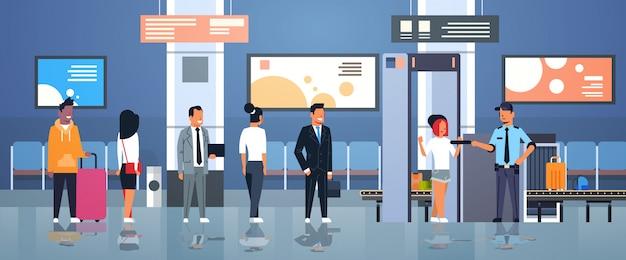 Ufficiale di polizia che controlla passeggeri e bagagli all'interno del terminale del dipartimento di controllo di sicurezza dell'aeroporto dello scanner completo del corpo dei raggi x del metal detector Vettore Premium