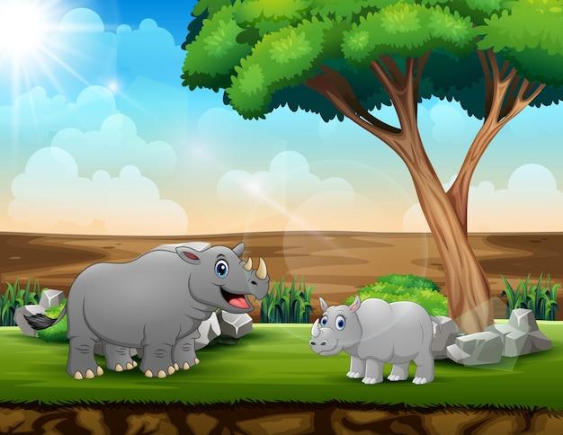Un grande rinoceronte con il suo cucciolo nel campo Vettore Premium