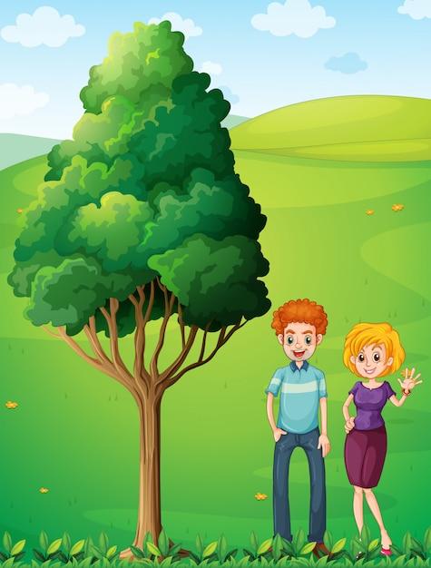 Una coppia in cima alla collina in piedi vicino all'albero Vettore gratuito