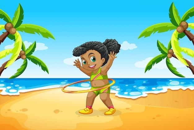Una ragazza gioca a hula hoop in spiaggia Vettore gratuito