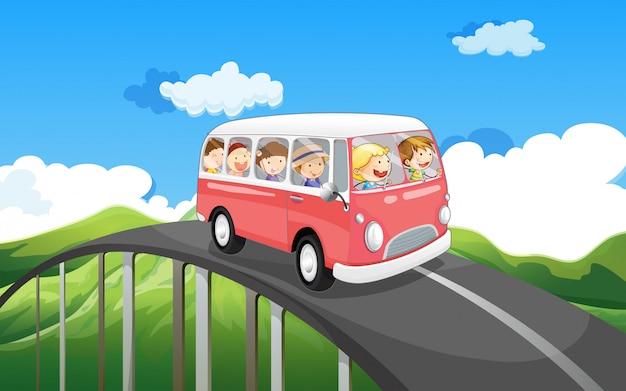 Uno scuolabus con bambini che viaggiano Vettore gratuito