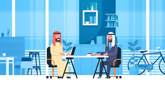 Uomini arabi di affari che si siedono alla scrivania nello spazio moderno di coworking che lavora insieme ai lavoratori musulmani nel centro dei colleghe Vettore Premium