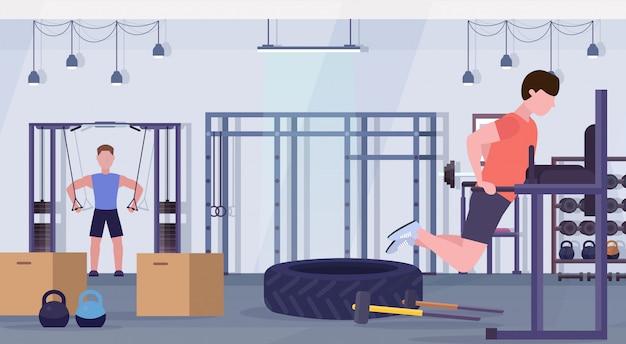 Uomini di sport che fanno le esercitazioni sui ragazzi dell'apparecchiatura di addestramento della barra parallela che risolvono nel crossfit della palestra che prepara concetto moderno di stile di vita sano interno dello studio del club di salute Vettore Premium