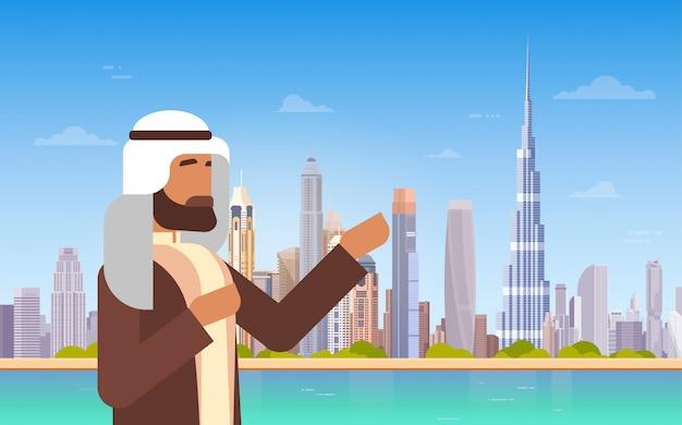 Uomo arabo che mostra panorama dell'orizzonte del dubai, viaggio d'affari di paesaggio urbano della costruzione moderna e turismo conce Vettore Premium