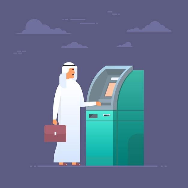 Uomo arabo che per mezzo della carta di credito che prende soldi dalla carta di credito, uomo d'affari islam che indossa grumo tradizionale Vettore Premium