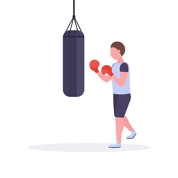 Uomo boxer facendo esercizi con il sacco da boxe facendo colpo diretto in guantoni da boxe rossi ragazzo combattente allenamento allenamento stile di vita sano concetto sfondo bianco Vettore Premium