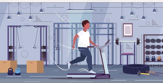 Uomo che corre sul tapis roulant sovrappeso ragazzo attività sportiva cardio allenamento allenamento perdita di peso concetto moderno palestra interno piano integrale orizzontale Vettore Premium
