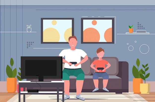 Uomo con bambino seduto sul divano utilizzando il joystick sovrappeso padre e figlio che maneggiano videogiochi in tv obesità stile di vita malsano concetto moderno soggiorno interno orizzontale a figura intera Vettore Premium