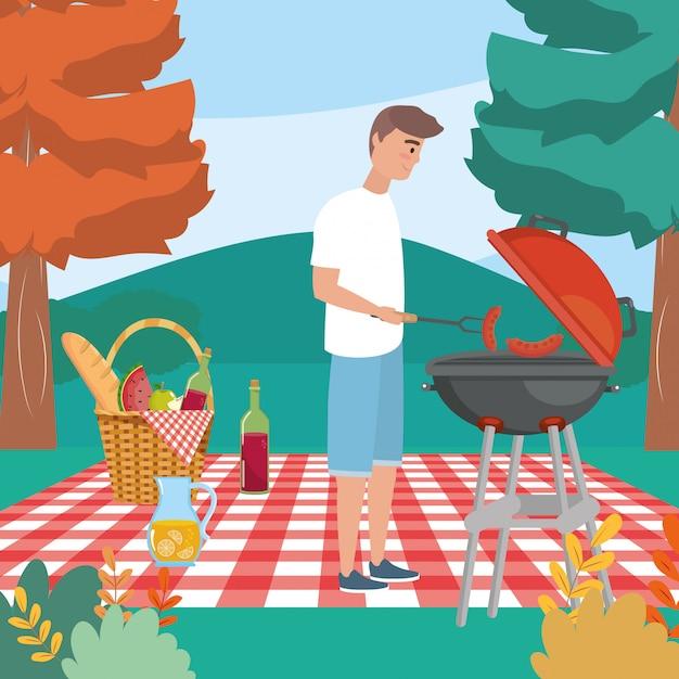 Uomo con grigliate e salsicce nella tovaglia con il cibo Vettore gratuito