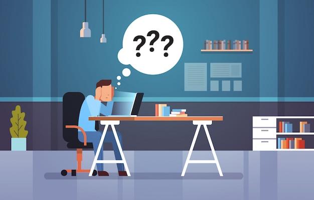 Uomo d'affari confuso usando il portatile sul posto di lavoro pensando a risposte Vettore Premium