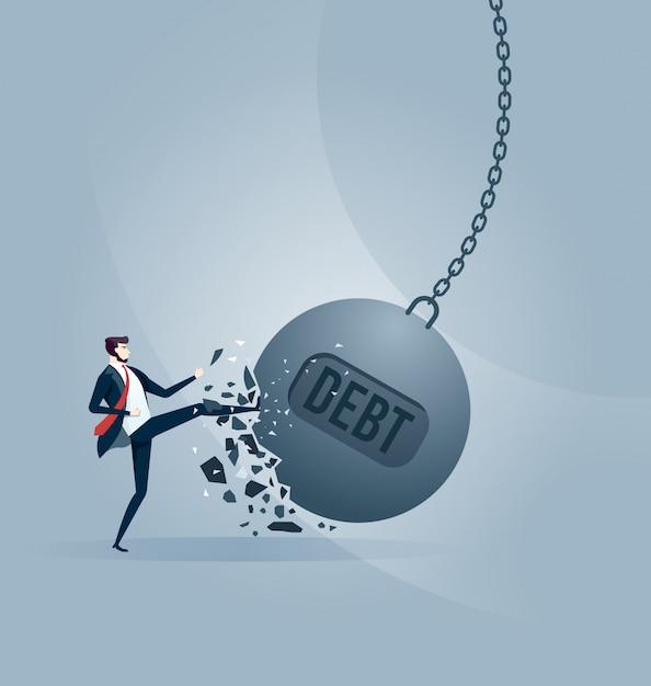 Uomo d'affari prende a calci una palla da demolizione gigante con una parola debito. Vettore Premium