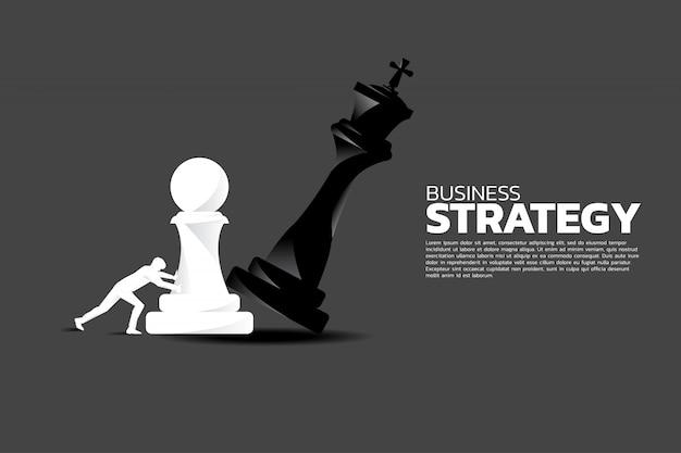 Uomo d'affari spingere pezzo di scacchi pegno a scacco matto il re. Vettore Premium