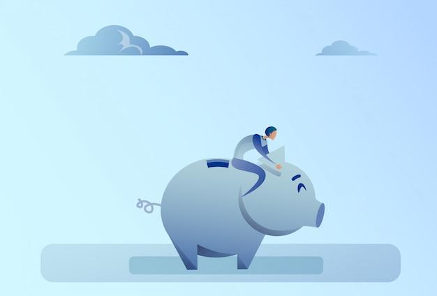 Uomo di affari che si siede sul concetto di risparmio dei soldi del porcellino salvadanaio Vettore Premium