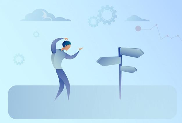 Uomo di affari sullo sguardo della strada trasversale al bordo del segno che sceglie concetto di direzione Vettore Premium