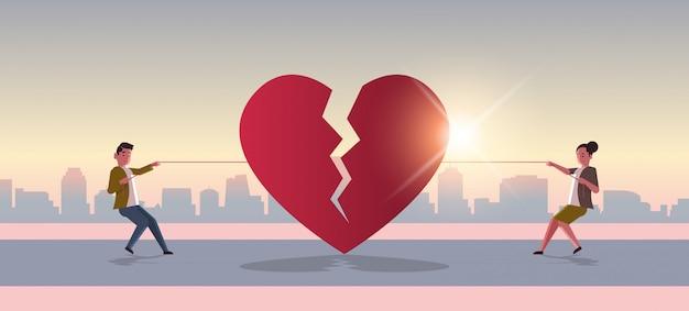 Uomo donna tirando la corda strappando il cuore spezzato rosso Vettore Premium
