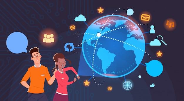 Uomo e donna sul globo del mondo con le icone di social media background internet e tecnologia moderna Vettore Premium