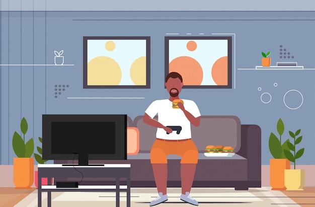 Uomo seduto sul divano a mangiare hamburger utilizzando il joystick game pad sovrappeso guy plays videogiochi in tv stile di vita malsano concetto soggiorno interno orizzontale a figura intera Vettore Premium
