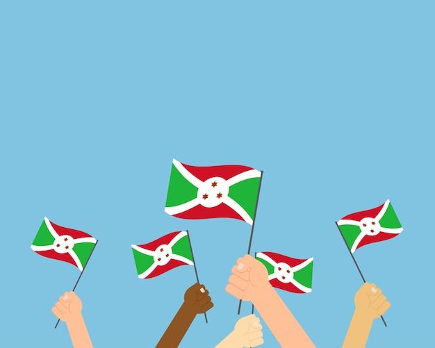 Vector l'illustrazione delle mani che tengono le bandiere del burundi Vettore Premium