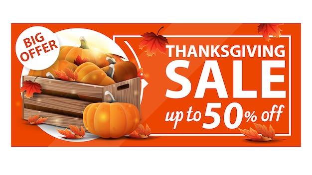 Vendita del ringraziamento, fino al 50% di sconto, banner web sconto arancione con casse di legno di zucche mature e foglie d'autunno Vettore Premium
