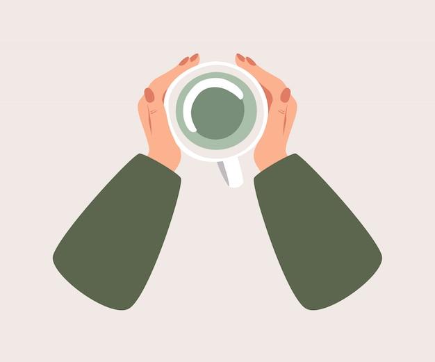 Vista dall'alto una tazza di tè verde riscalda una mano umana. Vettore Premium