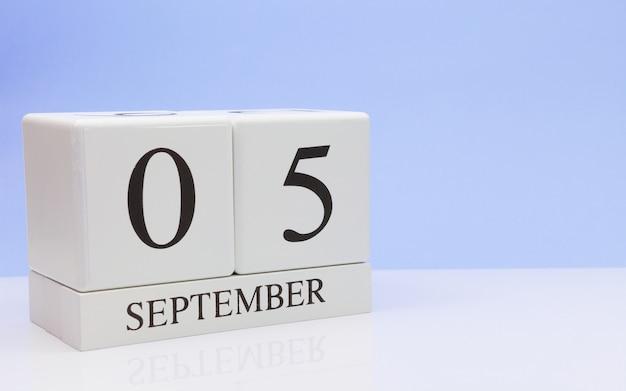05 september. dag 5 van de maand, dagelijkse kalender op witte tafel met reflectie Premium Foto