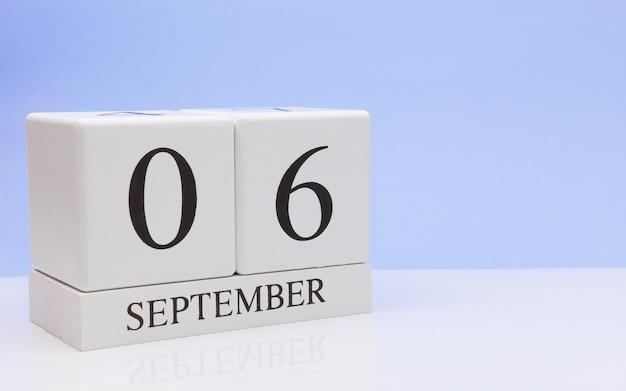 06 september. dag 6 van de maand, dagelijkse kalender op witte tafel met reflectie Premium Foto