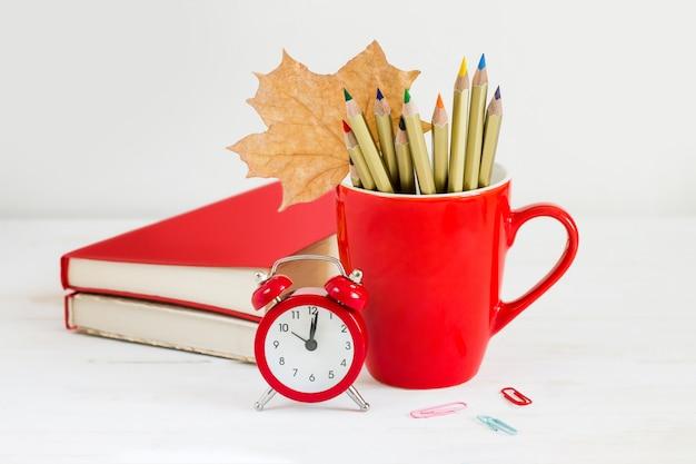 1 september concept. rode wekker, kop, kleurenpotloden, boeken en esdoornblad. terug naar school-concept Premium Foto