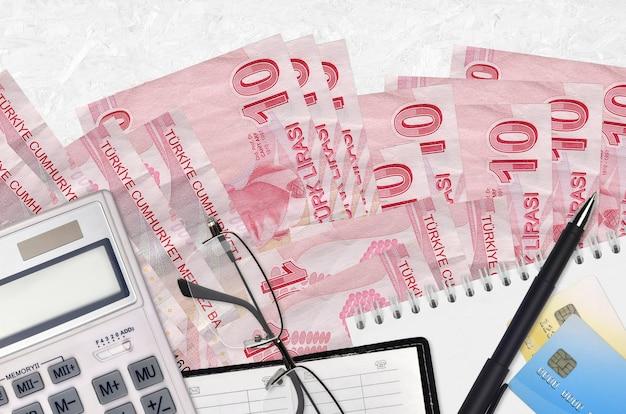 10 turkse lira's rekeningen en rekenmachine met bril en pen. belastingbetalingsseizoenconcept of investeringsoplossingen. Premium Foto