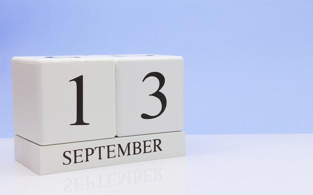 13 september. dag 13 van de maand, dagelijkse kalender op witte tafel met reflectie Premium Foto