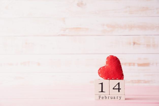 14 februari tekst op houten blok met rood hart op houten achtergrond. Premium Foto
