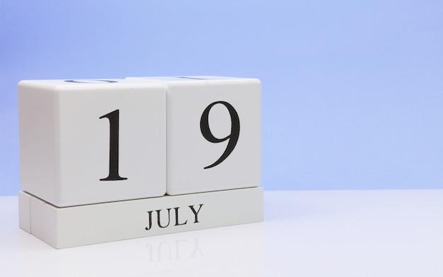 19 juli. dag 19 van de maand, dagelijkse kalender op witte tafel met reflectie, met lichtblauwe achtergrond. Premium Foto