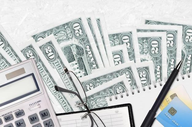 20 dollarbiljetten en rekenmachine met bril en pen. Premium Foto