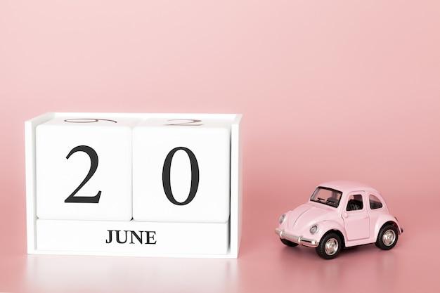 20 juni, dag 20 van de maand, kalender kubus op moderne roze achtergrond met auto Premium Foto