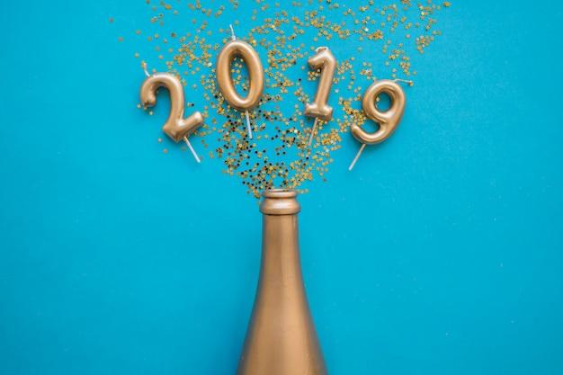2019 inscriptie van kaarsen met fles op tafel Gratis Foto