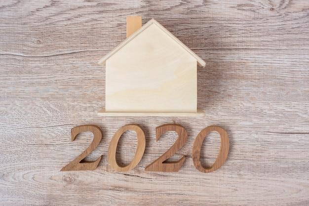 2020 gelukkig nieuwjaar met huismodel op houten tafel Premium Foto