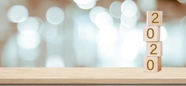 2020 gelukkig nieuwjaar wenskaart, houten kubussen met 2020 meer dan vervagen bokeh achtergrond met kopie ruimte Premium Foto