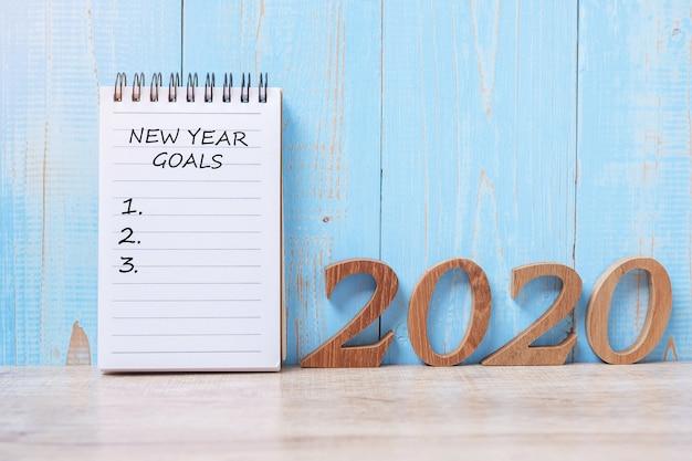 2020 gelukkig nieuwjaardoelenwoord op notitieboekje en houten aantal. Premium Foto