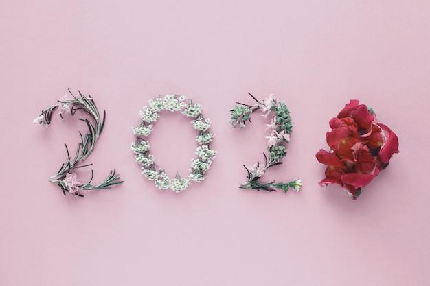2020 gemaakt van natuurlijke bladeren en bloemen op roze achtergrond, happy new year wellness en een gezonde levensstijl Premium Foto