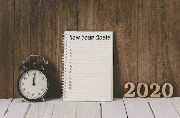 2020 houten tekst en nieuwjaarsdoelenlijst geschreven op notebook met wekker Premium Foto