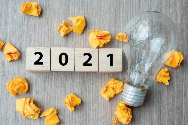 2021 houten kubusblokken en verkruimeld papier met gloeilamp Premium Foto