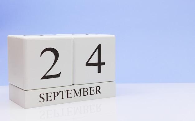 24 september. dag 24 van de maand, dagelijkse kalender op witte tafel met reflectie Premium Foto