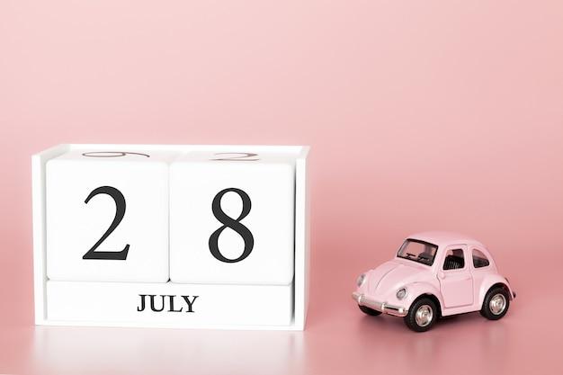 28 juli, dag 28 van de maand, kalender kubus op moderne roze achtergrond met auto Premium Foto