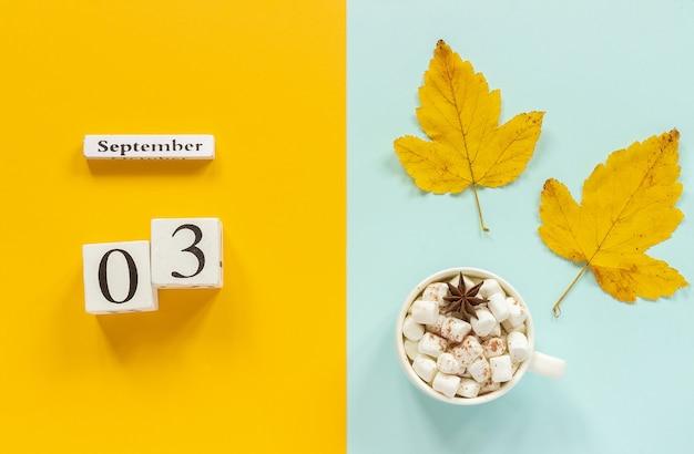 3 september, kopje cacao met marshmallows en gele herfstbladeren op gele blauwe achtergrond Premium Foto