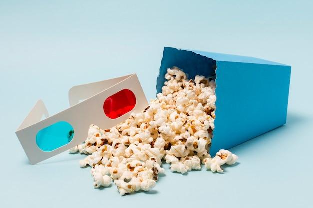 3d glazen dichtbij de gemorste popcorn van de doos op blauwe achtergrond Gratis Foto