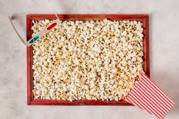 3d glazen en popcorn gemorst in houten frame op concrete achtergrond Gratis Foto