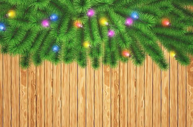 3d kerstboomtakken met lichten op een houten textuurachtergrond Gratis Foto