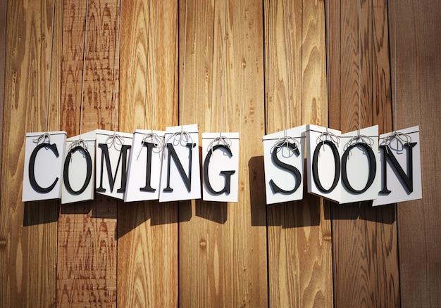 3d-weergave van letters die de woorden vormen die binnenkort aan touwtjes hangen tegen de achtergrond van een houten planken Premium Foto
